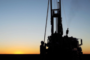 Silhouette of an oil drill rig against the sunset