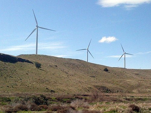 Three wind turbines on a grassy hill with blue skies