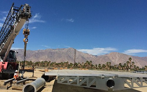 Installation of solar panel foundation in desert with mountains in distance