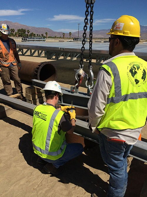 Three employees supervising pile load testing for solar panel foundation