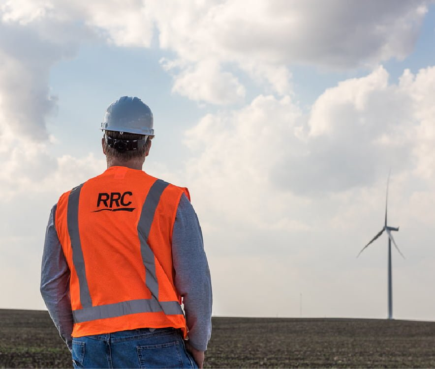 RRC employee in safety gear standing in field with single wind turbine in the background