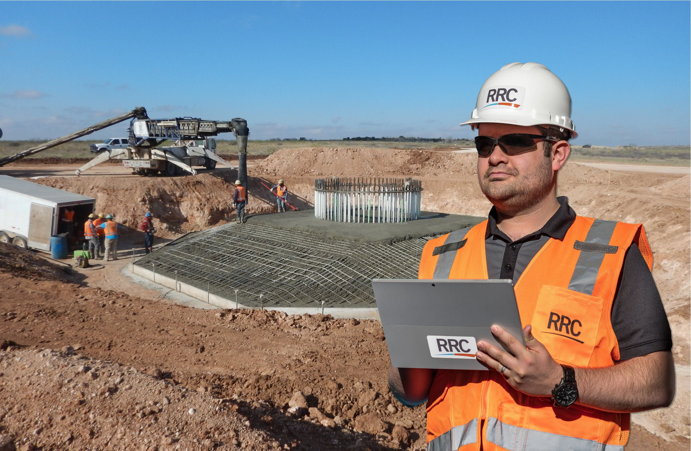 RRC employee in safety gear review information on tablet at wind foundation site