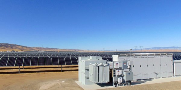 Unit substation transformer with field of solar panels in background