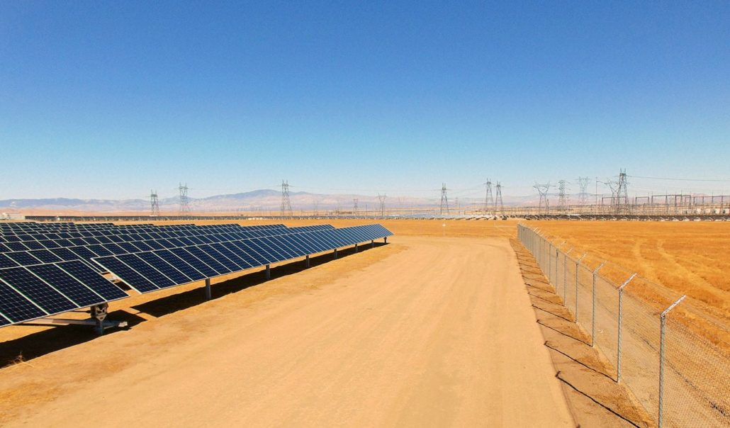 A row of solar panels next to an unpaved road with power lines in the background