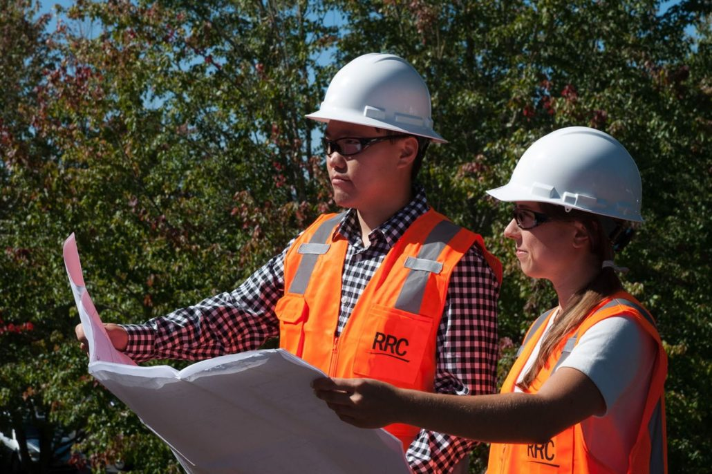 Two employees wearing safety equipment and reviewing plans