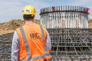 RRC employee in safety gear inspecting rebar foundation cage of wind turbine