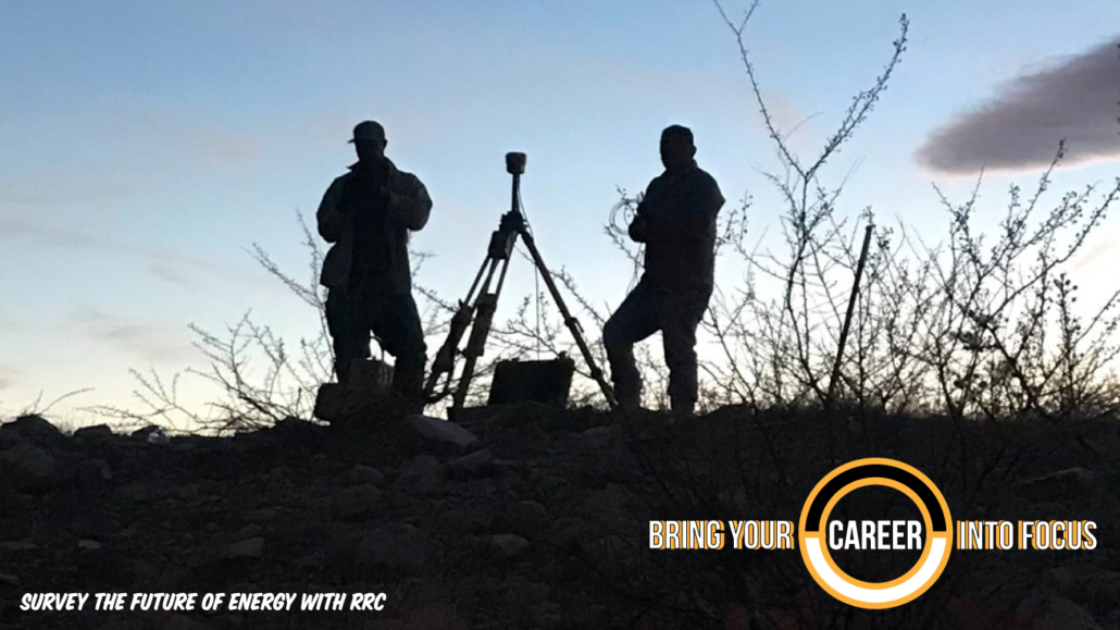 Silhouette of two surveyors in the field at sunrise