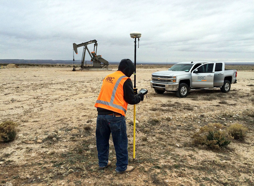 RRC surveyor with equipment in field in front of an oil pump and RRC company truck