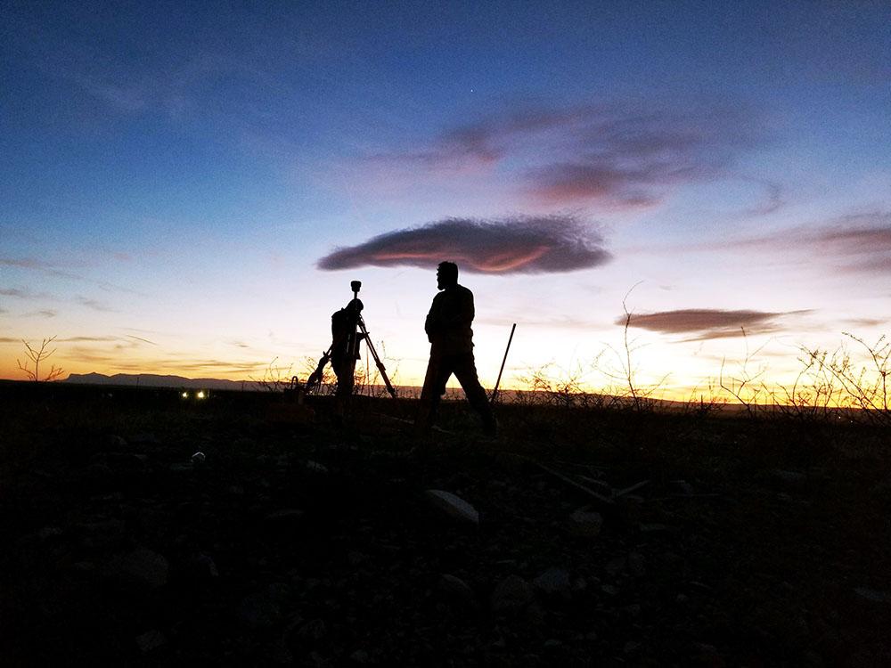Sunrise silhouette of surveyor in the field